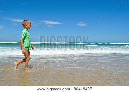 Young Boy Walking Along The Waters Edge