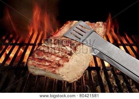 Tongs Holding Grilled Pork Ribs