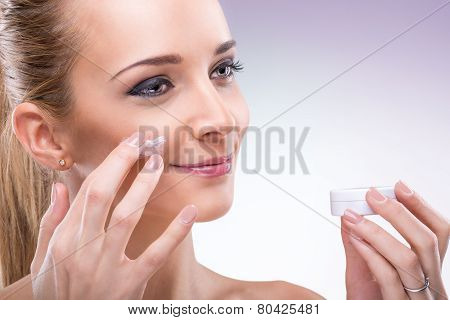 Beauty flawless skinned woman with face cream