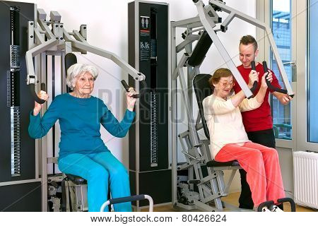 Old Women Exercising At Gym With Instructor
