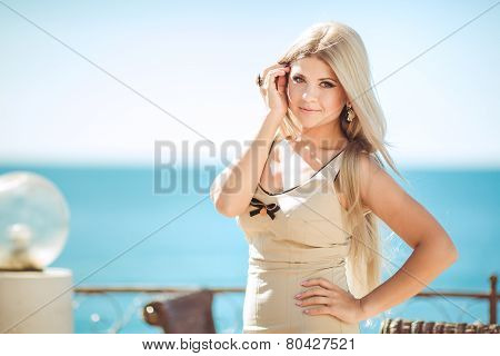 Beautiful woman on the balcony of the hotel overlooking the ocean.