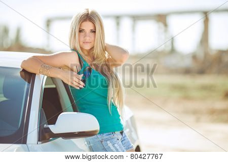 Bright woman - blonde, near white car.