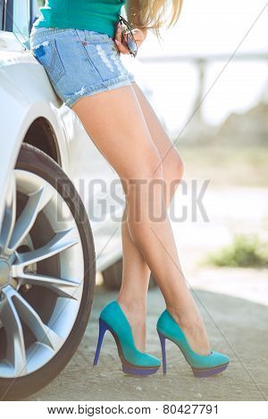 Beautiful female legs near the new car.