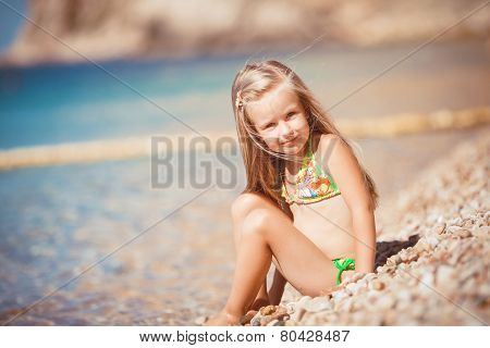 Little girl on the beach near the sea.