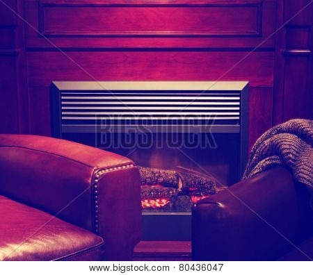 a comfortable cozy interior fireplace and cozy armchair in living room  of a living room space  toned with a retro vintage instagram filter effect