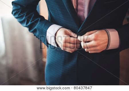 Men Fastens His Black Suit