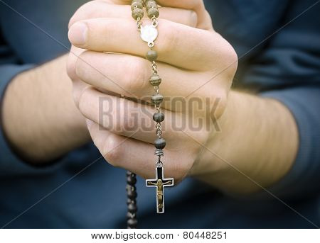 Man Prays With A Rosary In Hands