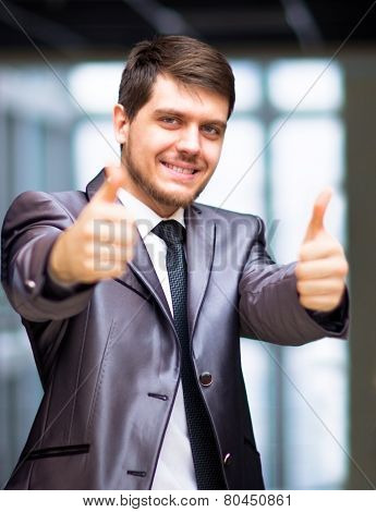 business man in urban city holding thumbs up