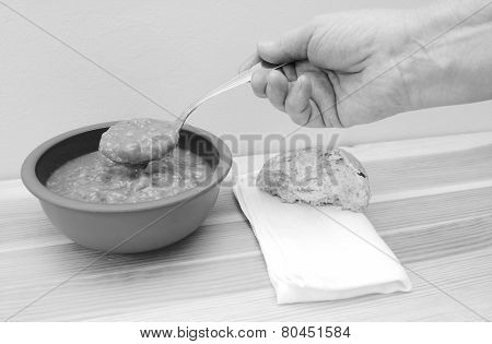 Hand Holds Spoonful Of Soup With Bread Roll And Napkin On Table
