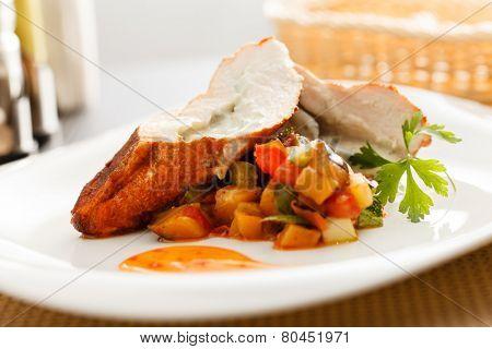 stuffed pork tenderloin roulade garnished with vegetables