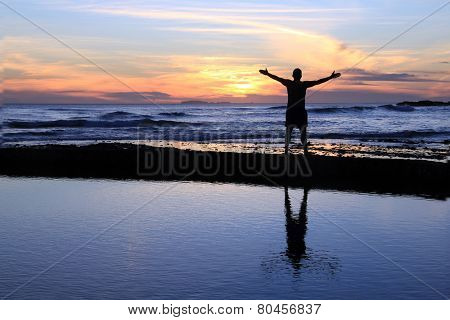 Silhouette of a man with outstretched arms at sunset on a beach.