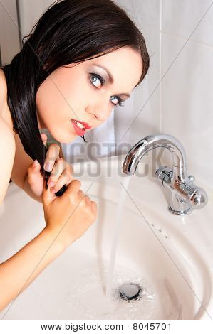 Beautiful brunett woman is washing her hair