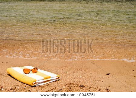 Sunglasses And Towel Next To The Sea.