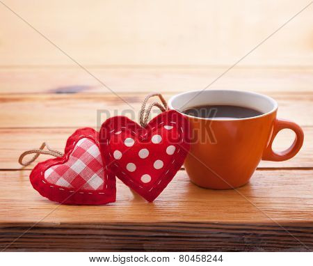 Cup Of Coffee And Handmade Heart Fabric On Wooden Table