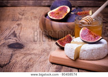 Camembert Cheese With Honey And Figs On A Wooden Board.
