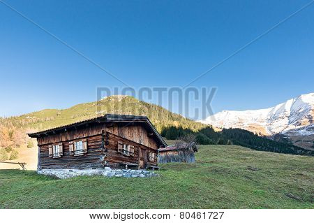 sun burned timber chalet hut on austrian mountains at fall