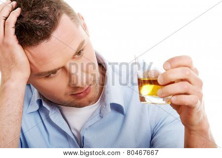Yound man in depression, drinking whisky