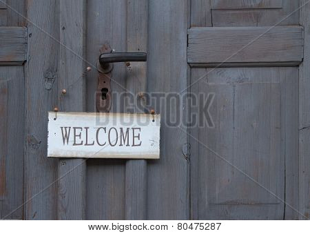 Welcome Sign Hanging On An Old Wooden Door