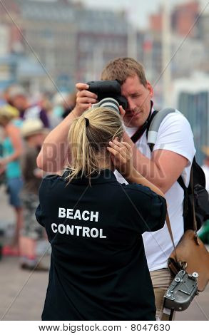 Male Photographer Taking Photo Of Female Beach Attendant
