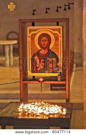 TABGHA, ISRAEL - JANUARY 21, 2012: Magnificent old icon of Jesus Christ, and table with burning candles. The ancient church on Sea of Galilee