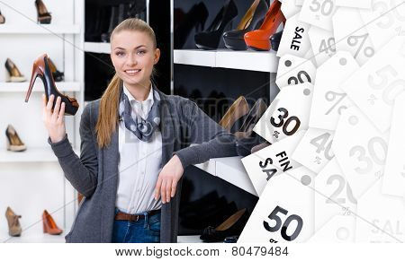Woman with shoe in hand chooses stylish pumps looking at the shelves with numerous pumps on sale