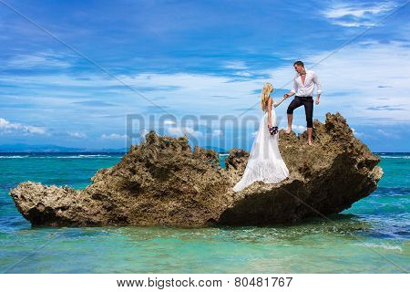 Happy Bride And Groom Having Fun On A Tropical Beach Under The Palm Trees. Tropical Sea In The Backg
