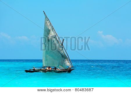Wooden sailboat  (dhow) on the clear turquoise water of Zanzibar island