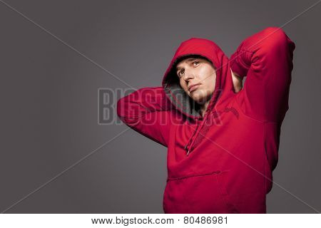 Portrait Of Masculine Strong Tanned Caucasian Man In Red Hoody Jacket. Posing Against Gray Studio Ba