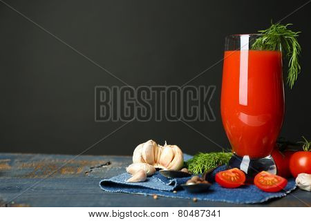 Glass of tasty tomato juice and fresh tomatoes on table, on grey background