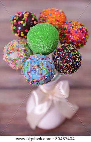 Sweet cake pops in vase on wooden background