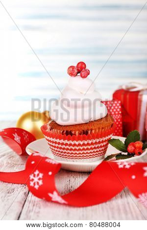 Cup-cake on saucer with Christmas decoration on color wooden table light background