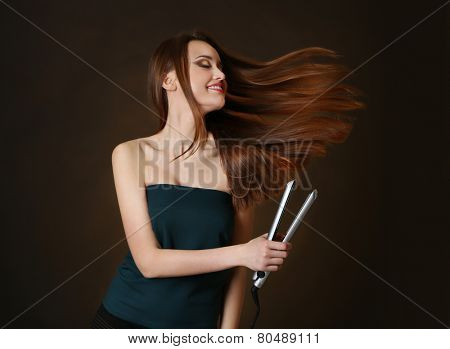Beautiful young woman with long hair using hair straighteners on dark brown background