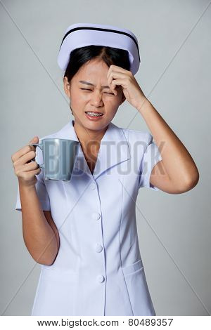 Young Asian Nurse Got Headache With A Cup Of Coffee