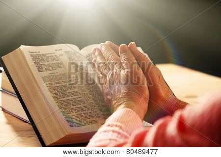 Hands of old woman with Bible on table and dark background