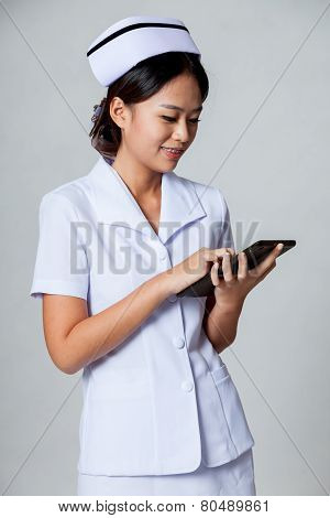 Young Asian Nurse Surfing Net With Tablet Pc