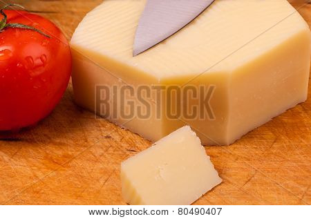 Piece Of Cheese With A Tomato On A Wodden Board