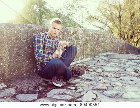 Young man on the old stone bridge with harsh sunlight in background