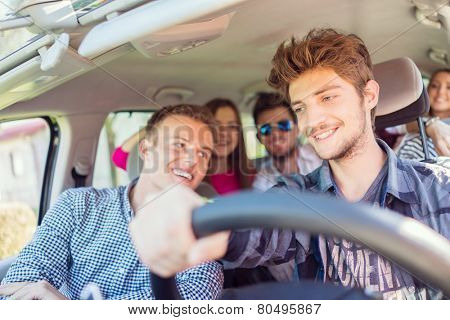 Young people having vacation enjoying fun driving car