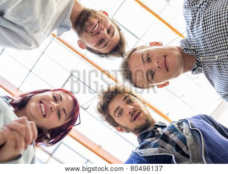 Image of business friends discussing brainstorming and ideas at meeting inside beautiful modern building place in circle holding each other