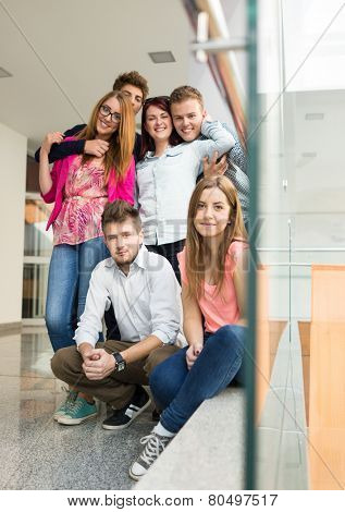 Group of young peopl standing on fence railing indoors and talking