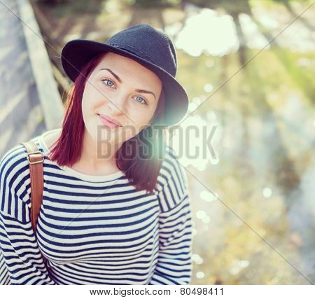 Young woman with hat having fun in nature on river