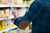 stock photo of grocery store  - Smiling Young Man Using Mobile Phone While Shopping In Shopping Store - JPG