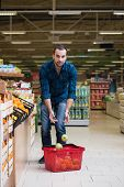 picture of department store  - Handsome Young Man Shopping For Fruits And Vegetables In Produce Department Of A Grocery Store  - JPG
