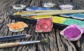 stock photo of messy  - Closeup of messy used water color paint box and paint brush - JPG