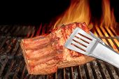 image of tong  - Tongs Holding Grilled Pork Ribs - JPG