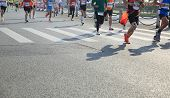 Постер, плакат: Unidentified marathon athletes legs running on city road