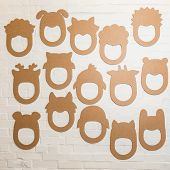stock photo of laughable  - Set of cardboard masks on a white brick wall  - JPG