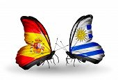 stock photo of spanish money  - Two butterflies with flags on wings as symbol of relations Spain and Uruguay - JPG