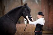 foto of horse girl  - Portrait of the girl and black horse. The girl communicates with a beautiful horse. Equestrian sport.
