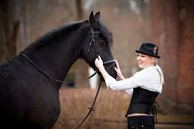 stock photo of horse girl  - Portrait of the girl and black horse. The girl communicates with a beautiful horse. Equestrian sport. ** Note: Soft Focus at 100%, best at smaller sizes - JPG